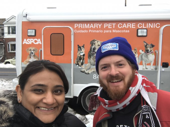 Image of two people, a woman and a man, in front of an orange van.