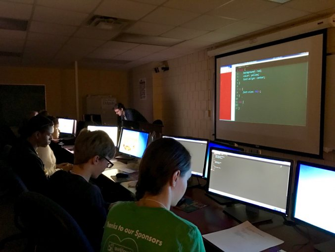 Young people working at a series of computers in front of a projector screen in a dark room
