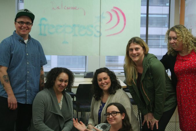FreePress and Echo teams pose for a picture in front of handmade FreePress logo.